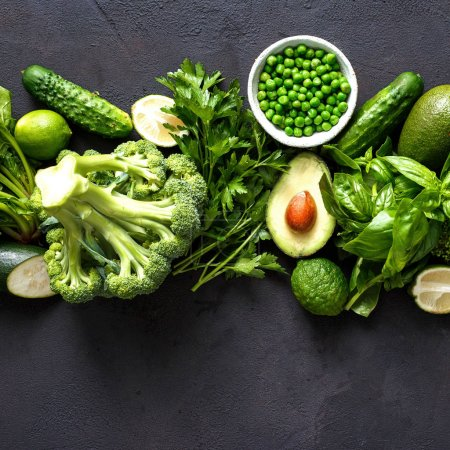 Raw healthy food, clean eating vegetables: cucumbers, alfalfa, zucchini, spinach, basil, green peas, dill, parsley, avocado, broccoli, limes on dark stone background, top view.