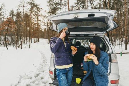 Dziewczyny w zimie nosić na śnieżnego dnia w lesie zimą w samochodzie o talk i picia kawy