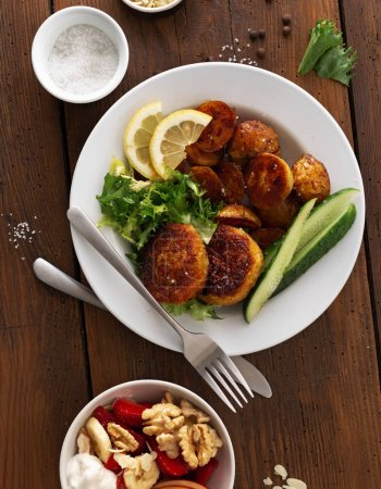 Photo for Dinner plate with vegetarian food. Fresh vegetarian cutlets with new potatoes and salad on wooden table top view - Royalty Free Image