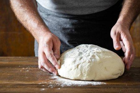 Mann bereitet Teig für selbstgebackenes Brot zu