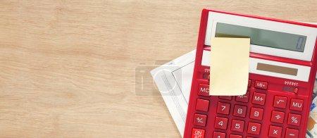 Photo pour Calculatrice rouge avec note et facture de services publics facture sur table en bois avec espace de copie - image libre de droit