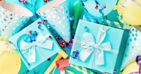 Photo pour Fond de célébration avec boîte cadeau, banderoles de fête colorées, confettis et chapeaux de fête d'anniversaire vue de dessus - image libre de droit
