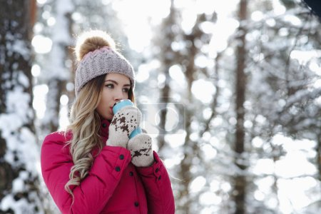 Photo for Pretty woman in burgundy coat hold blue thermo cup and drink hot coffee or tea and warm up in winter forest. Winter holiday concept - Image - Royalty Free Image