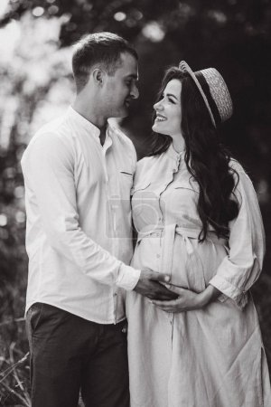 Photo for Monochrome photo of romantic couple, standing and holding by hands, enjoying  and looking to each other. Pregnant woman with long wawe hair and hat on  her head, wearing in light dress and smiling. - Royalty Free Image