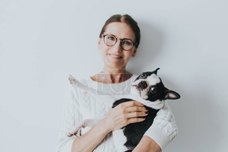 Portrait of happy young adult in good mood  at home. Happy housewife fondling french bulldog with pleasure. Copy space, family concept.Indoor portrait of smiling woman with dog on grey background.