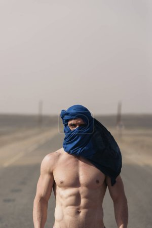 Portrait of caucasian man with turban looking at camera in desert.