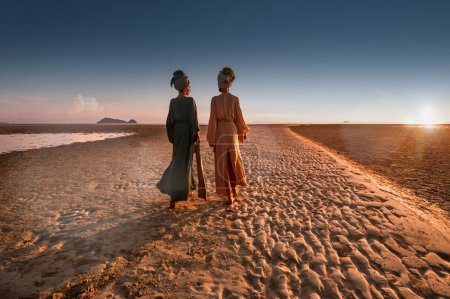 Photo for Silhouette of two young beautiful girls in turban on the beach at sunset - Royalty Free Image