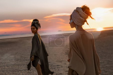Photo for Two young beautiful girls in turban walking on the beach at sunset - Royalty Free Image