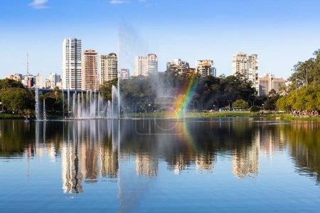 Photo pour Un grand groupe de personnes regardant l'arc-en-ciel formé par les gouttes de la fontaine du parc Ibirapuera et en arrière-plan les bâtiments résidentiels de luxe, Sao Paulo, Brésil . - image libre de droit