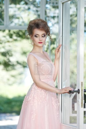 Beautiful bride in long pink dress with bright terrace