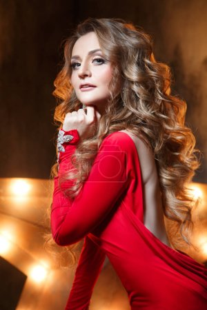 Beauty fashion portrait of elegant woman in red. Evening make-up and chic curls.
