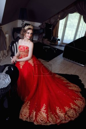 Beautiful woman in a chic red dress and crown in a chic interior.