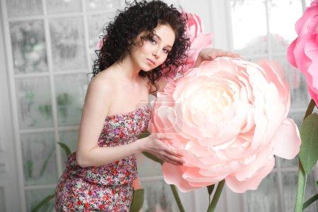 Photo pour Une belle fille brune mince tient une énorme fleur de pivoine du papier . - image libre de droit