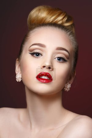 Beauty fashion portrait of a beautiful girl with bright makeup and red lipstick with rhinestones on her lips.