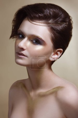 Fashion beauty portrait of woman with shiny makeup on beige background.