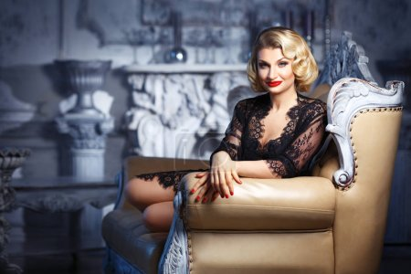 vintage portrait of elegant blonde with waved hairstyle sitting on chair