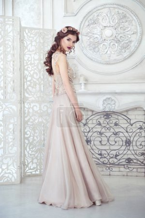 Beautiful girl in a long dress developing in pastel colors