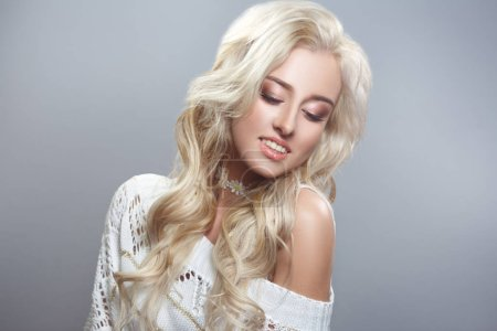 Beauty portrait of a sunny sexy blond girl with chic curls isolated on a gray background.