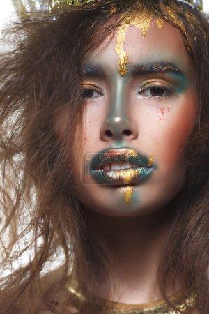 Photo pour Frappant la fille avec le maquillage créatif d'ecchymoses et de plumes d'or sur fond blanc - image libre de droit