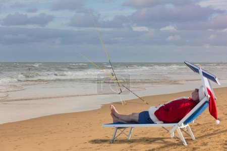 Santa Claus sleeping on the beach bed. Christmas fishing.