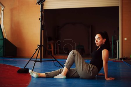 Photo for Charming brunette girl sits near luminaire on tatami. Backstage shooting - Royalty Free Image
