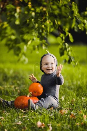 close-up portrait of a beautiful boy in in dragon costume  a  with in a yellow autumn garden park  smiling sunny day celebrates Halloween with pumpkins