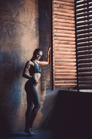 Photo for Fitness strength training workout concept background - muscular bodybuilder sexy sport girl doing exercises in gym in the boxing gloves - Royalty Free Image