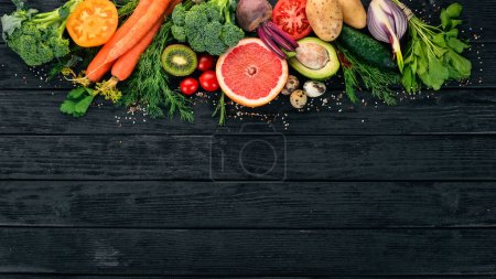 Photo pour Alimentation saine. Fruits et légumes. Sur un fond noir en bois. Vue de dessus. Espace copie. - image libre de droit