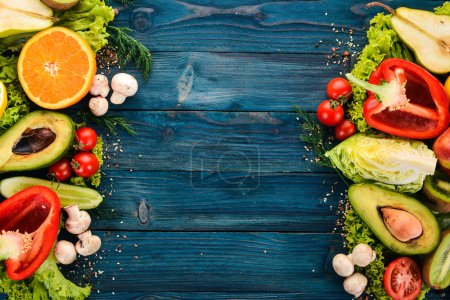 Photo for Assortment of fresh vegetables and fruits. Healthy food On a blue wooden background. Top view. Copy space. - Royalty Free Image