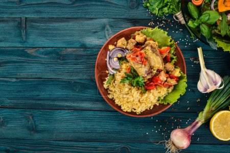 Photo for Bulgur with meat, paprika, cherry tomatoes, and vegetables. On a wooden background. Top view. Copy space. - Royalty Free Image