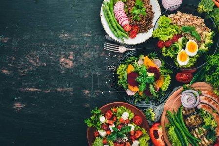 ensemble de nourriture. Poitrine de poulet grillée, saucisses, aubergines, tomates cerises, légumes frais. Sur une table en bois noir. Vue de dessus. Espace libre pour le texte .