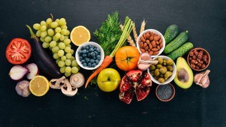 Photo pour Propre choix de manger sainement: légumes, fruits, noix, baies et champignons, persil, épices. Sur un fond noir. Espace libre pour le texte. - image libre de droit