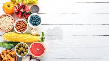 Photo for Healthy food on a white wooden table. Fresh vegetables, fruits, nuts, berries, mushrooms. Top view. Free space for text. - Royalty Free Image