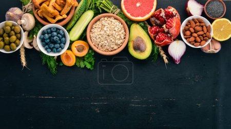 Photo pour Aliments sains sélection d'aliments propres : légumes, fruits, noix, baies et champignons, persil, épices. Sur fond noir. Espace libre pour le texte . - image libre de droit