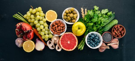 Photo for Healthy food clean eating selection: Vegetables, fruits, nuts, berries and mushrooms, parsley, spices. On a black background. Free space for text. - Royalty Free Image