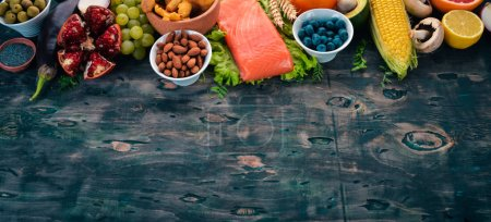 Photo for Healthy food. Fish, nuts, fresh vegetables and fruits. On an old wooden table. Top view. Free space for text. - Royalty Free Image