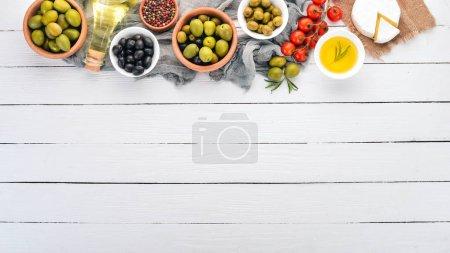 Photo pour Olives vertes et olives noires, huile, pain, fromage et collations. Cuisine italienne. Sur une table en bois blanc. Vue de dessus. Espace libre pour le texte . - image libre de droit