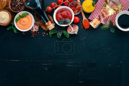 Photo for Set the sauces on a black wooden background. Ketchup, mayonnaise, mustard, soy sauce, barbecue sauce, pepper and spices. Top view. Free space for text. - Royalty Free Image
