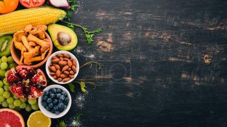 Aliments sains sélection d'aliments propres : légumes, fruits, noix, baies et champignons, persil, épices. Sur fond noir. Espace libre pour le texte .