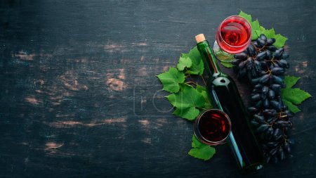 Photo for Red wine in a bottle with a glass and grapes. On a black wooden background. Free space for text. Top view. - Royalty Free Image