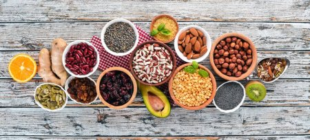 Photo for Superfoods Healthy food. Nuts, berries, fruits, and legumes. On a white wooden background. Top view. Free copy space. - Royalty Free Image