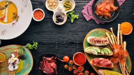 Photo for A set of dishes. Pumpkin soup, avocado sandwich, prosciutto, and mushrooms. Top view. Free space for your text. On a wooden background. - Royalty Free Image