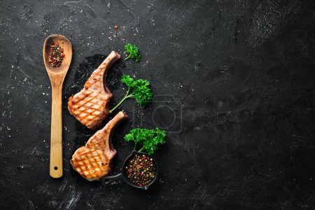 Photo for Barbecue pork steak on the bone with spices and herbs. Top view. Free space for your text. - Royalty Free Image