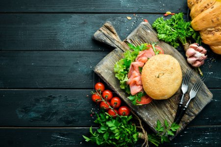 Photo for Burger with salmon, tomatoes and onions. Breakfast. Top view. Free space for your text. - Royalty Free Image
