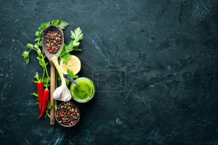Photo for Green parsley sauce, olive oil and spices. Ingredients for chimichurri sauce. On a black background. Top view. free space for your text. - Royalty Free Image