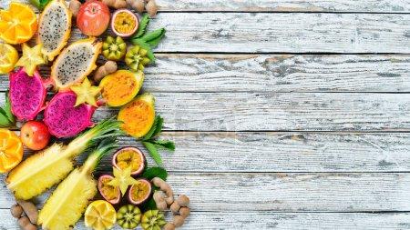 Foto de Frutas tropicales - Maracuya, piña, fruta de dragón, kiwi y cactus sobre un fondo blanco. Vista superior. Espacio libre para texto . - Imagen libre de derechos