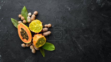 Photo for Kiwano and papaya on a wooden board. Top view. Free space for text. - Royalty Free Image