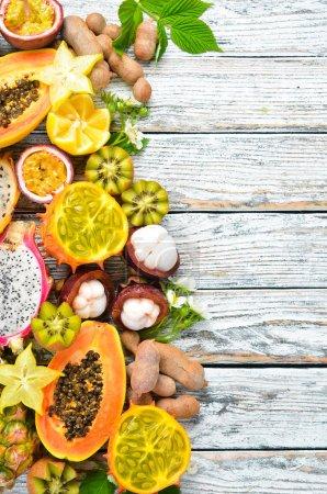 Photo pour Fruits tropicaux sur fond blanc : papaye, mangoustan, cactus, pytahaya, ananas. Vue de dessus. Espace libre pour le texte . - image libre de droit