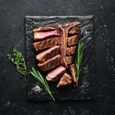 Photo for Beef T-Bone steak on a black table. Top view. Free space for text. - Royalty Free Image