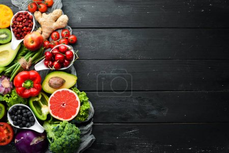 Photo for Fresh vegetables and fruits on a black background. Vitamins and minerals. Top view. Free space for your text. - Royalty Free Image